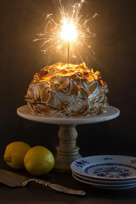 vertical image low FODMAP lemon meringue cake with sparkler