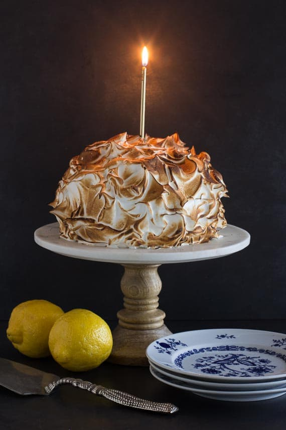 vertical low FODMAP lemon meringue cake with blue and white plates