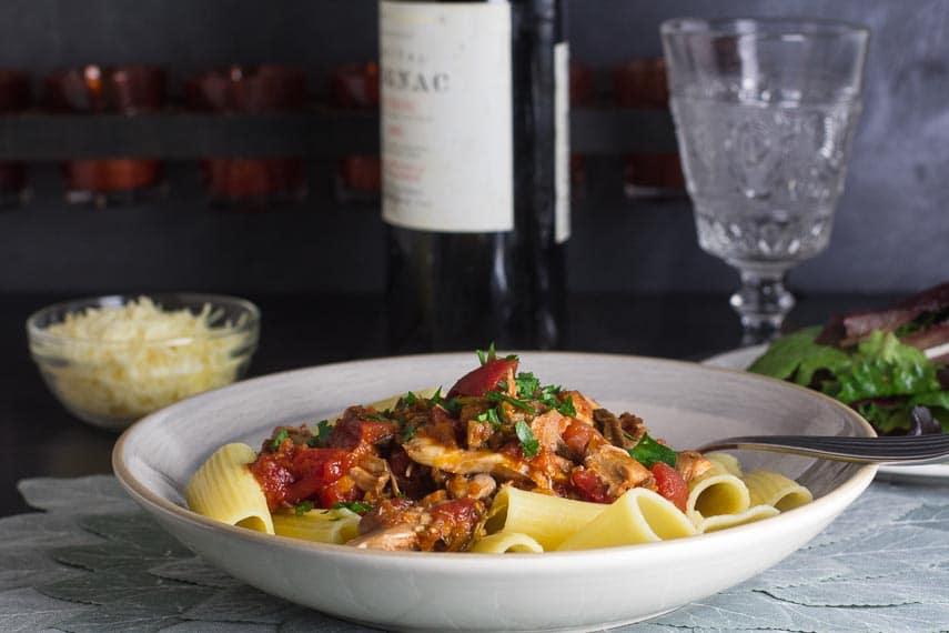 Low FODMAP Braised Chicken & Mushroom Ragu in grey bowl with fork alongside; Parmesan, wine and salad in background