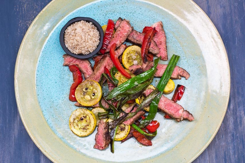 Low FODMAP Grilled Rib Eye with Smoked Salt and Charred Vegetables on ceramic plate against a blue background; overhead view