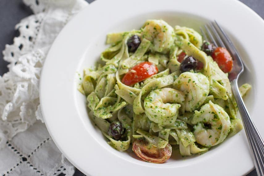 low FODMAP Parsley pesto with pasta, shrimp, tomatoes and olives in a white bowl