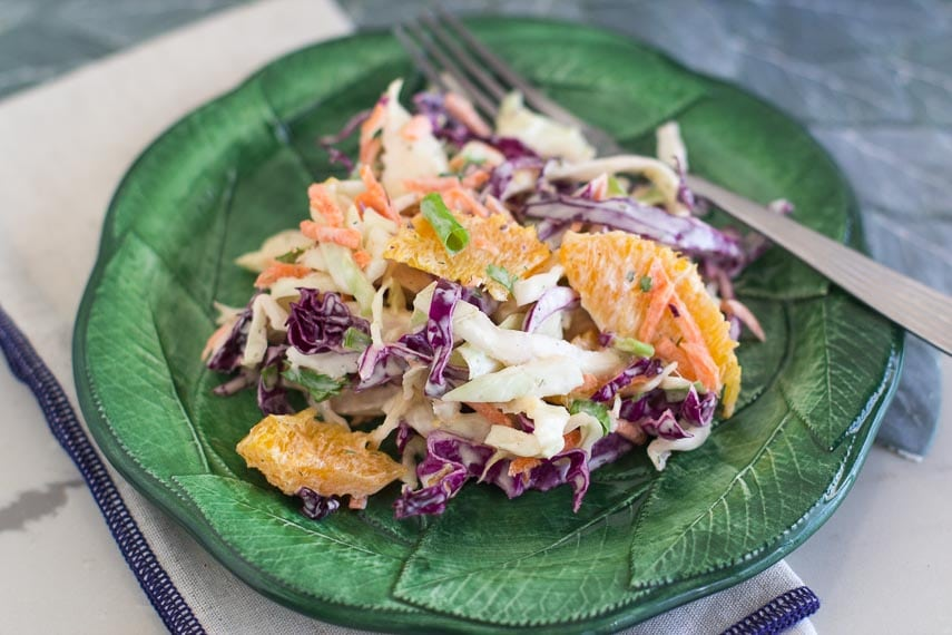 closeup of Low FODMAP Citrus Slaw with Creamy Grapefruit Dill Dressing on green plate