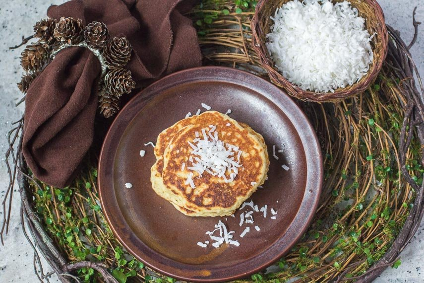 high overhead view of Low FODMAP Browned-Butter Coconut Pancakes on brown plate with brown cloth napkin on a rustic twig placemat