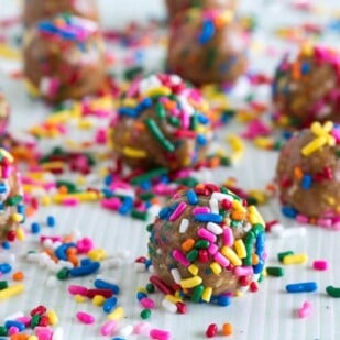 low FODMAP Birthday Cake Balls on pale surface with sprinkles all over