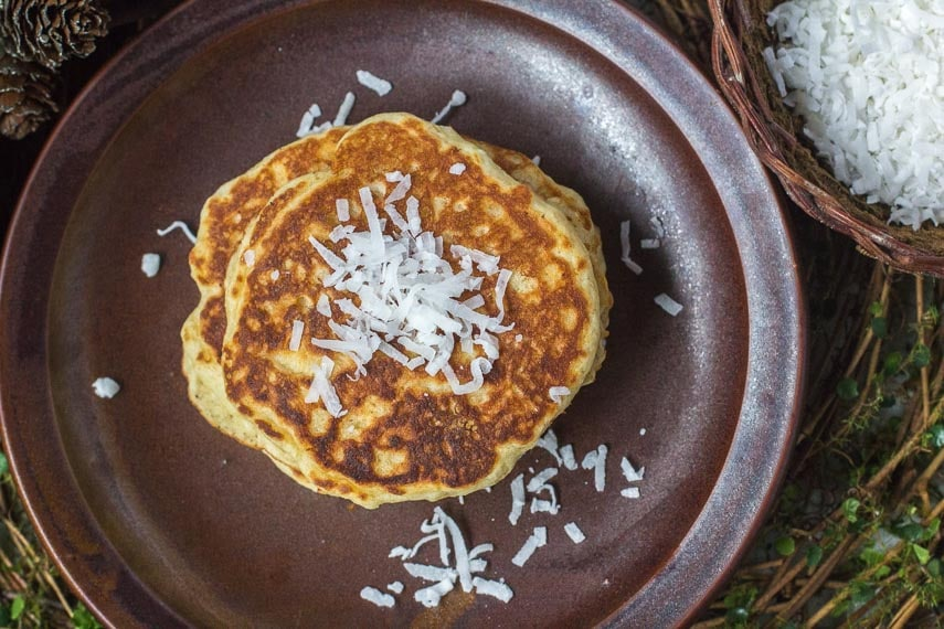 overhead image of Low FODMAP Browned-Butter Coconut Pancakes on a brown dish, with coconut in a dish alongside
