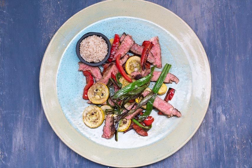 overhead view of Low FODMAP Grilled Rib Eye with Smoked Salt and Charred Vegetables on a blue and beige ceramic plate