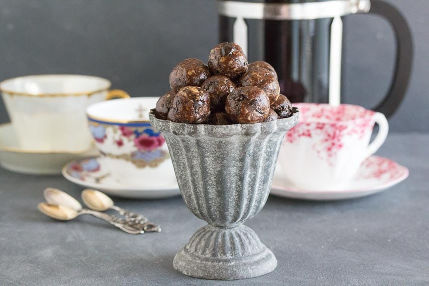 Low FODMAP Mocha Espresso Power Balls in a grey aluminum footed dish; coffee cups, French press coffee pot and spoons in background