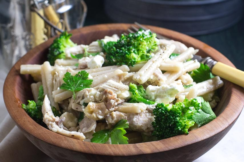 Low FODMAP Quick Pasta with Chicken, Broccoli & Goat Cheese in a wooden bowl with antique bone-handled fork