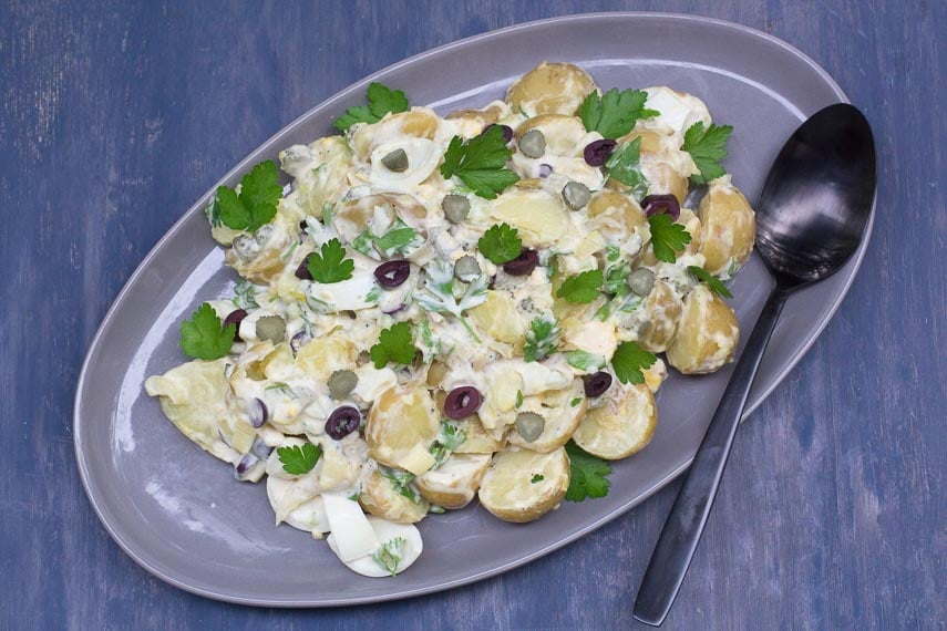 Low FODMAP Tangy Potato & Egg Salad with Olives & Pickles on a grey oval platter against a blue backdrop