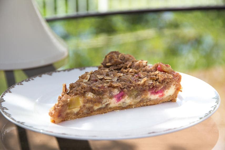 Slice of Low FODMAP Rhubarb Cheesecake Tart on white plate, oustide on glass table in grassy yard