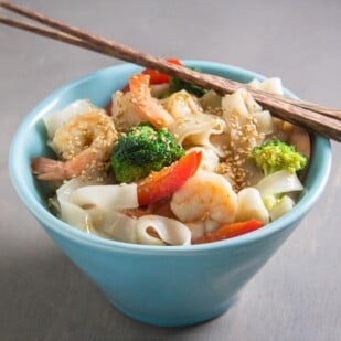 aqua bowl of low FODMAP shrimp and broccoli with noodles; chopsticks on top of bowl edge