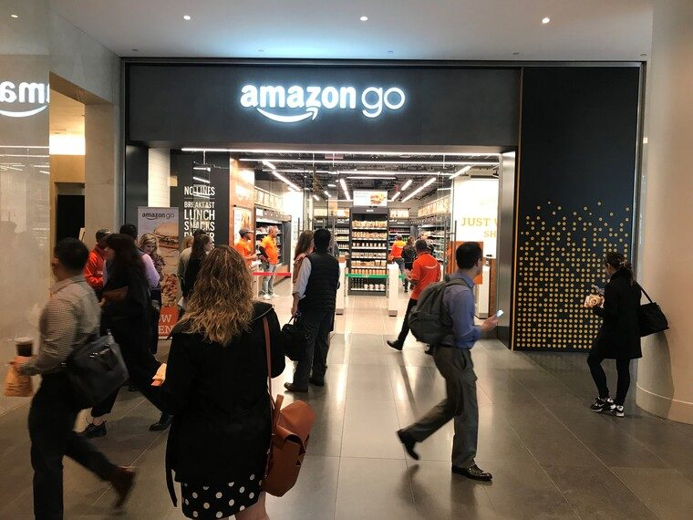 People walking in front of the open door of the Amazon Go store in NYC