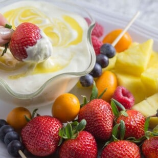 Low FODMAP Lime cheesecake dip in a decorative clear glass bowl; fruit alongside for dipping
