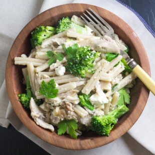 Low FODMAP Quick Pasta with Chicken, Broccoli & Goat Cheese in a wooden bowl with antique fork alongside