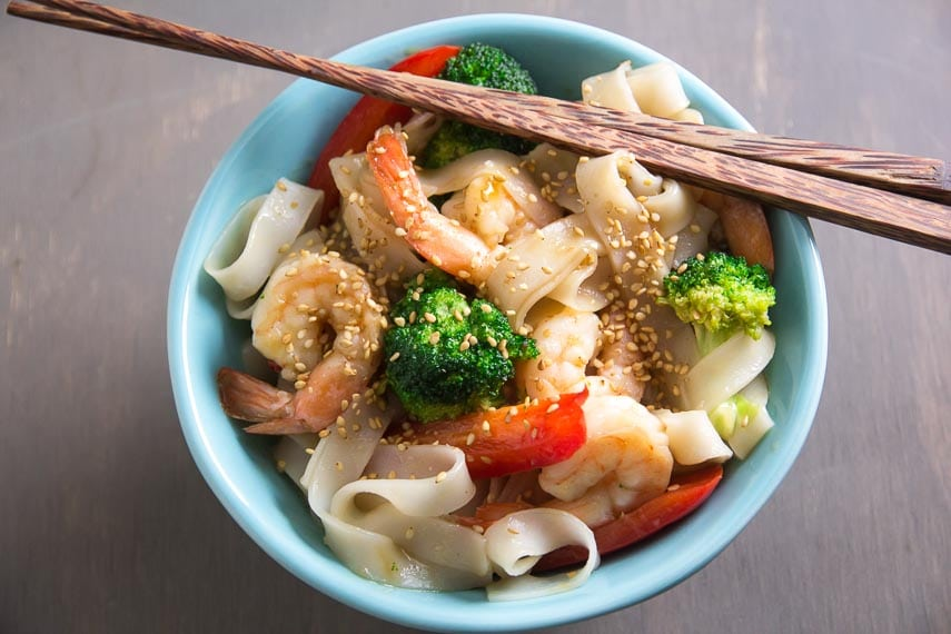 overhead shot of aqua bowl of low FODMAP shrimp and broccoli with noodles; chopsticks on top of edge of bowl