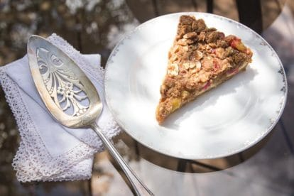 overhead shot of slice of Low FODMAP Rhubarb Cheesecake Tart on white plate, oustide on glass table_