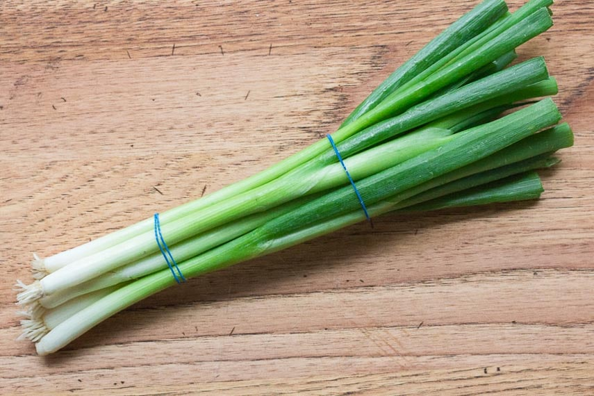 scallion bunch on wooden board