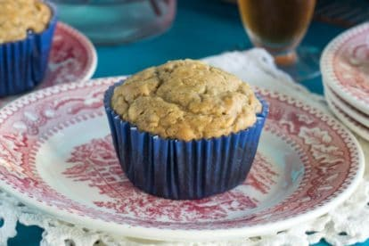 Low FODMAP High Protein Peanut Butter Muffins in a blue paper wrapper on a red and white antique plate