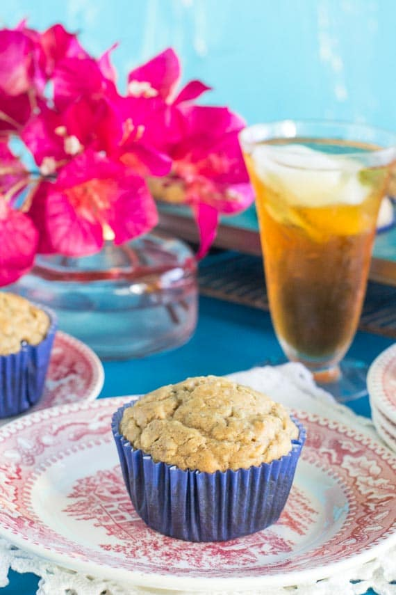 Low FODMAP High Protein Peanut Butter Muffins in a blue paper wrapper on a red and white antique plate; iced tea