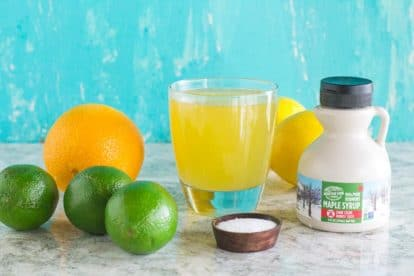 Maple Lime Low FODMAP Sports drink in a glass surrounded by ingredients against an aqua backdrop_