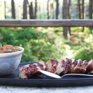 Quick Grilled Pork Tenderloin sliced on a black platter on the deck with grilled tomato peach salsa alongside