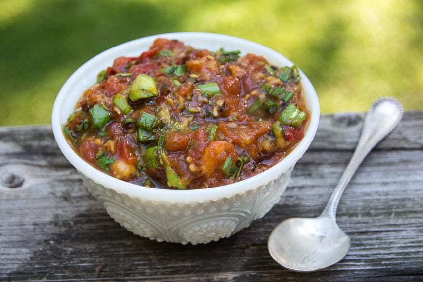 White bowl containing grilled tomato and peach salsa with spoon alongside