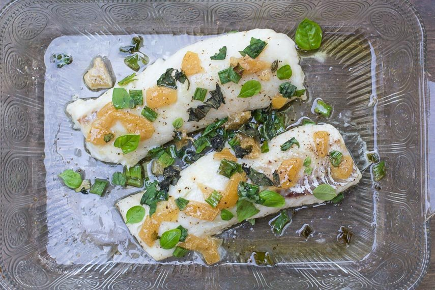 cod with preserved lemons & basil in decorative glass dish on brown surface