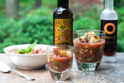 gazpacho in a bowl, garnished with basil, and two sizes of clear glasses for sipping; two kinds of sherry vinegar in background