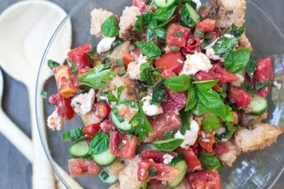 overhead Low FODMAP Panzanella with Tomatoes, Cucumbers & basil in a glass pedestal dish with wooden servers alongside