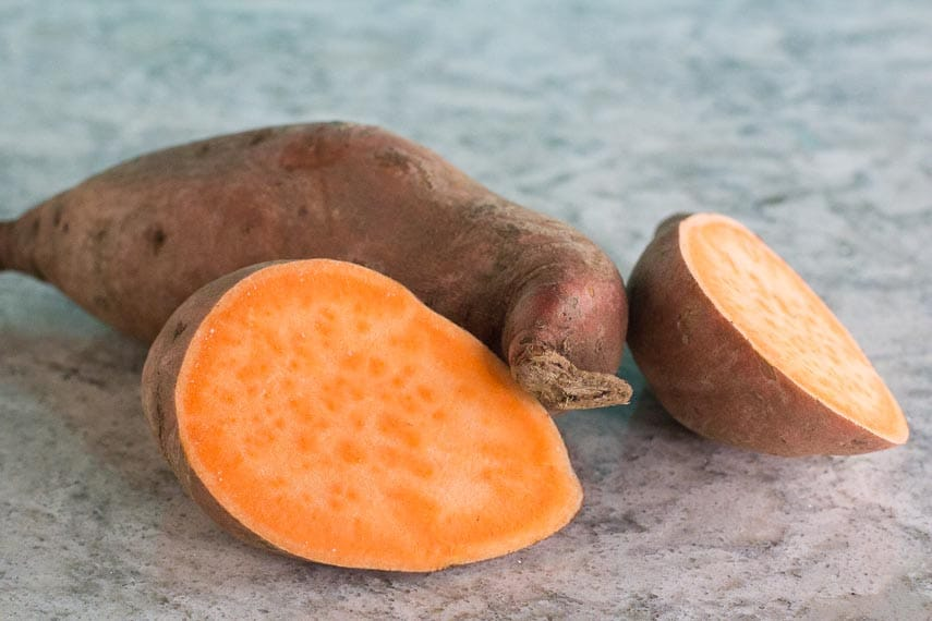 sweet potato, whole and cut open, on grey quartz surface