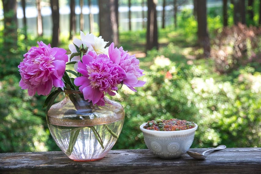 white bowl of grilled salsa alongside pink glass vase of peonies