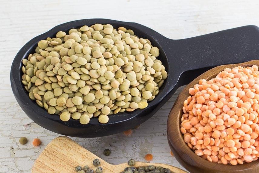 Green (brown) lentils in a black wooden scoop