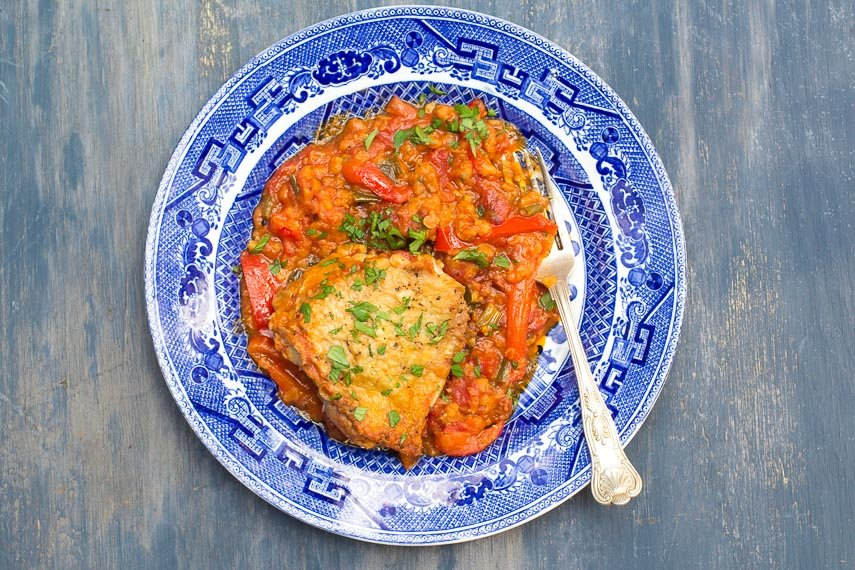 Low FODMAP Chicken & Lentils on a blue and white plate and blue painted background