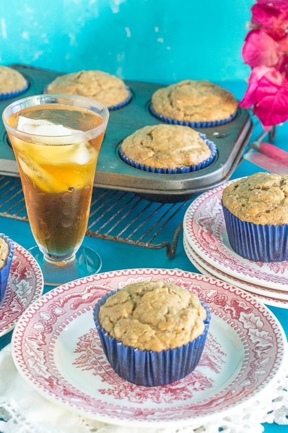 Low FODMAP High Protein Peanut Butter Muffins in a blue paper wrapper on a red and white antique plate with a glace of iced tea
