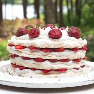 Low FODMAP Strawberry Coconut Meringue Cake on white wooden plate, outside on the deck