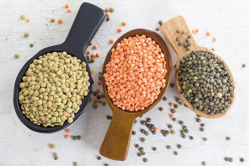 Three kinds of lentils in wooden scoops, on a white painted wooden surface