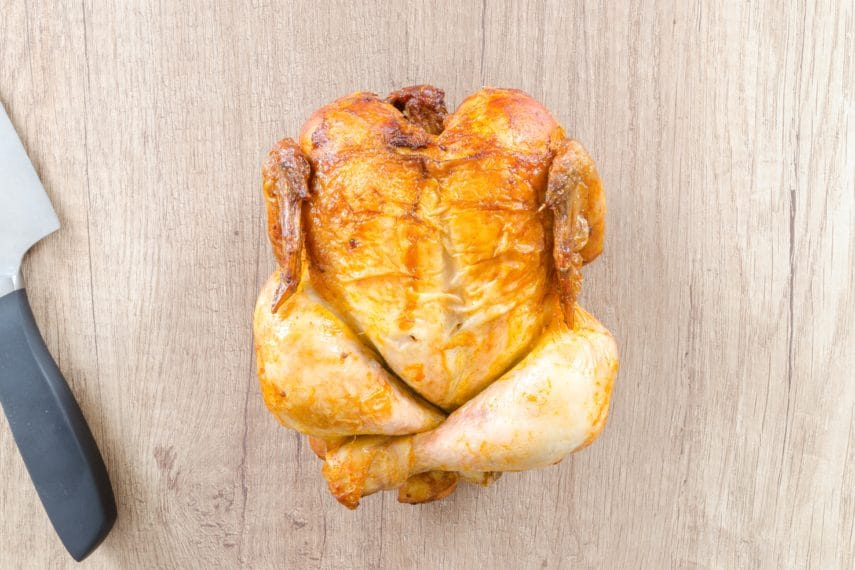 a rotisserie chicken on a wooden board with a knife alongside it