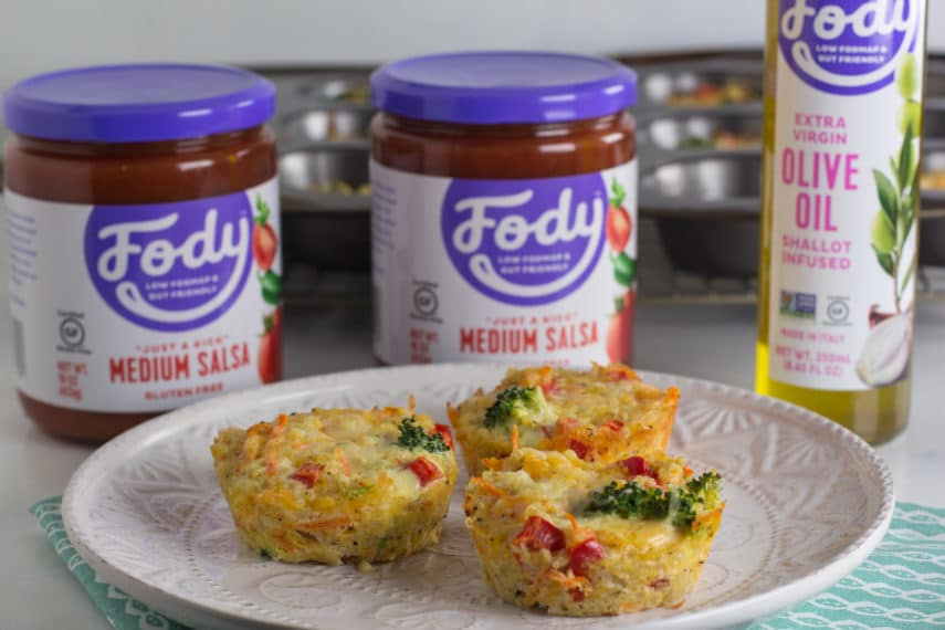3 vegetable and cheese egg cups on a white plate in front of 2 jars of salsa and a bottle of olive oil