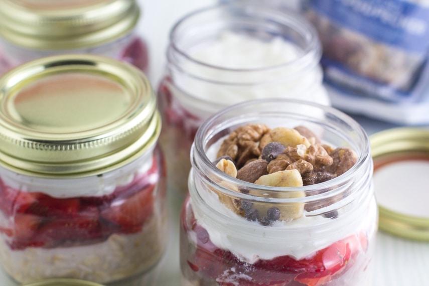 small glass jars filled wth layers of fruit, yogurt and trail mix