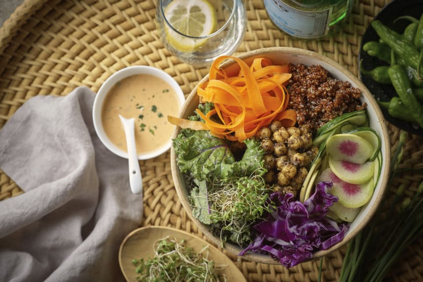 A bowl with fresh vegetables, chickpeas, grains and sprouts, next to a small bowl of dressing. All on a wicker tray.