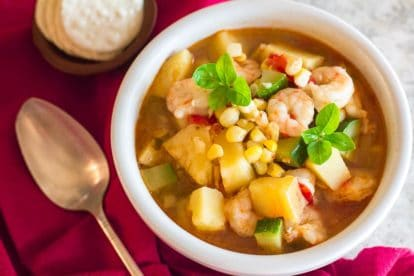 Low FODMAP Shrimp & Corn Chowder in white bowl; crackers and spoon alongside