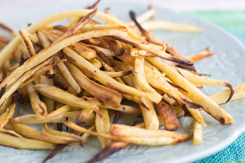 closeup of low FODMAP parsnip fries on light plate