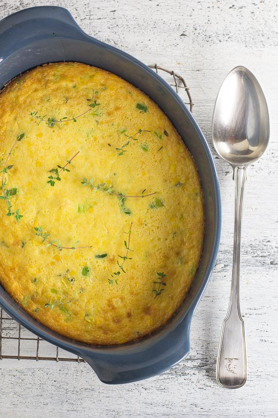 low FODMAP corn pudding with silver serving spoon alongside on painted white wooden surafce