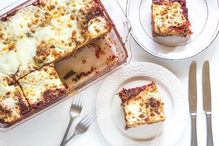 overhead view of hearty low FODMAP eggplant parmesan in pan and on white plate