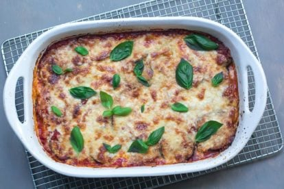 overhead view of low FODMAP eggplant parmigiana in white casserole on cooling rack