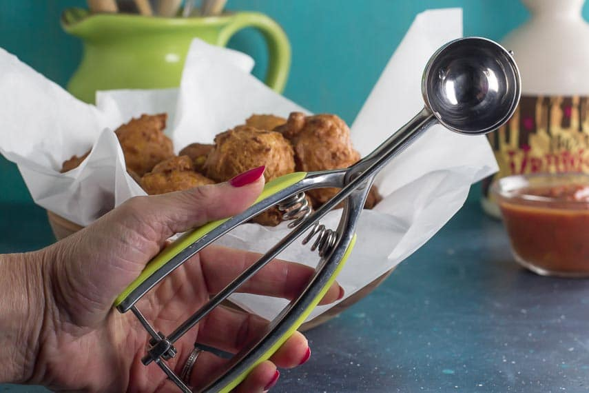 scoop for making low FODMAP corn fritters held in hand