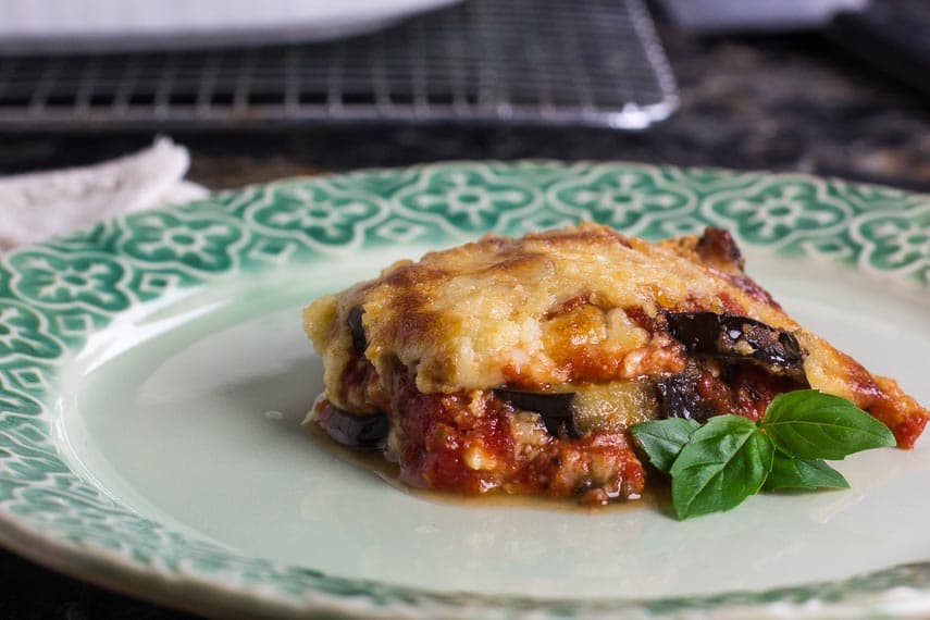side view of low FODMAP eggplant parmigiana on green decorative plate