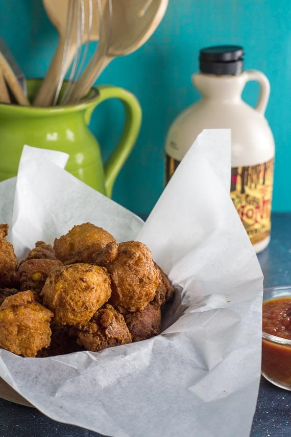 vertical image of low FODMAP corn fritters in a parchment paper lined bowl