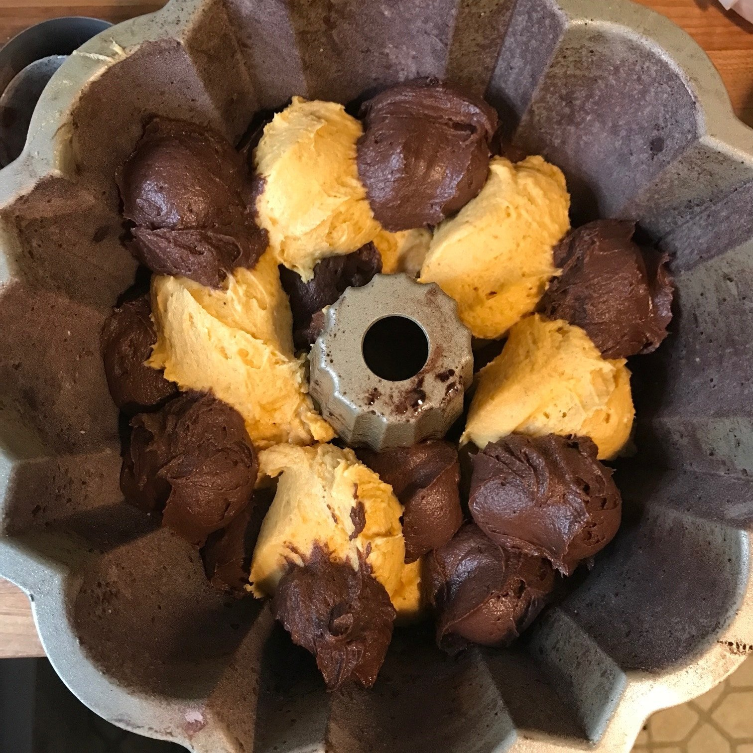 Pumpkin and cocoa batters being placed into Bundt pan