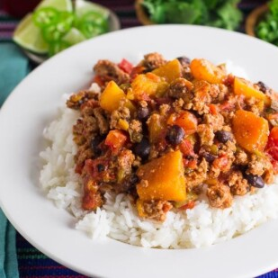 Low FODMAP Turkey Chili with Winter Squash & Beans with rice in a white bowl